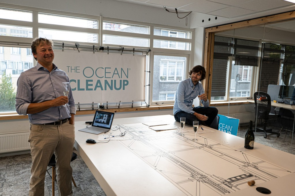 two men stand next to a table with The Ocean Cleanup banner in background