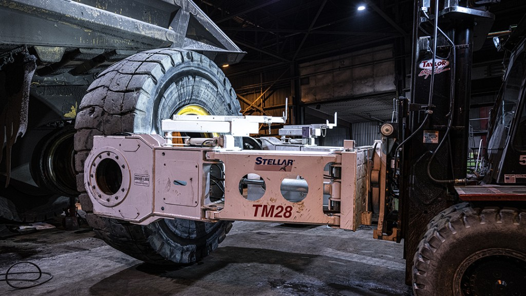 Stellar mining tire manipulator hooked to a mining machine