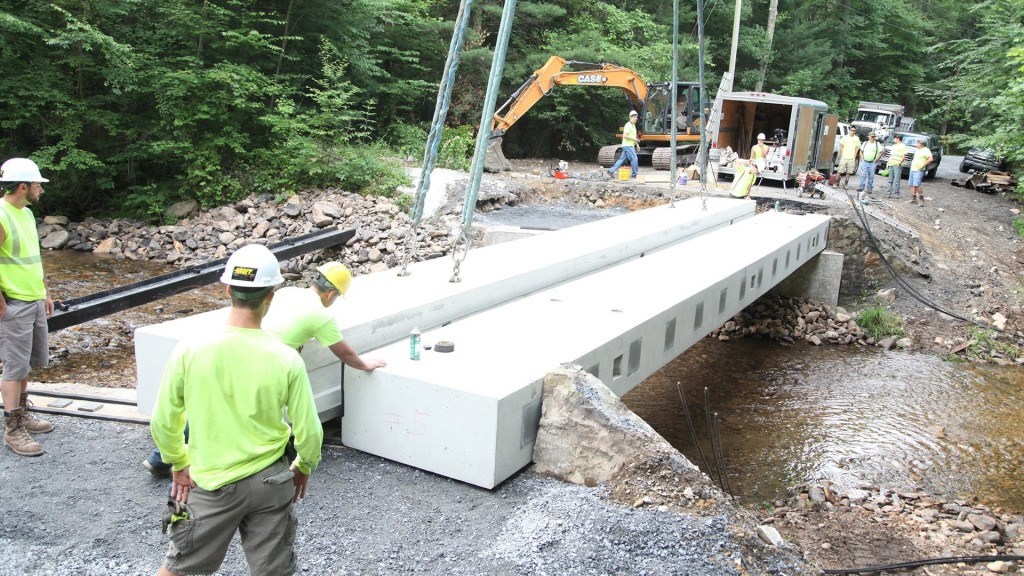 men work on building a bridge across a narrow river