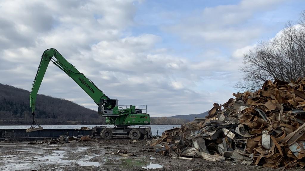 Sennebogen 840 M Material Handler at work in a junkyard next to a river