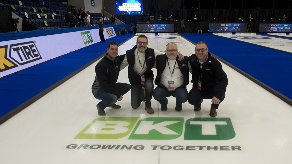 people pose in a crouching position on a curling rink in front of BKT logo
