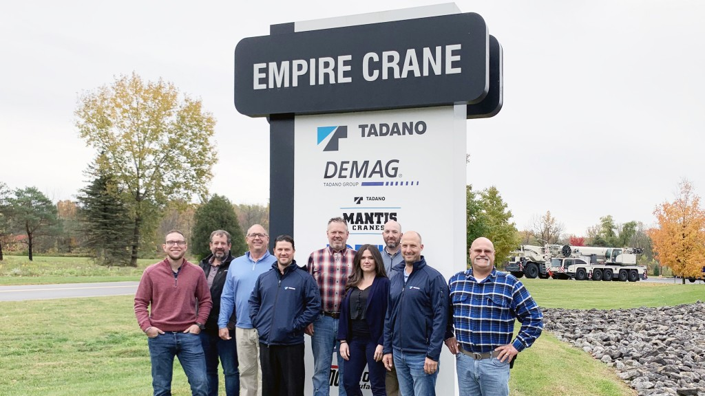 Empire Crane and Tadano representatives stand underneath Empire Crane sign