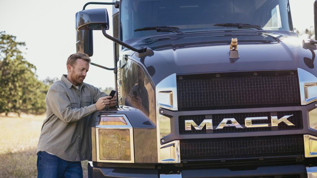 man texts on phone next to Mack truck