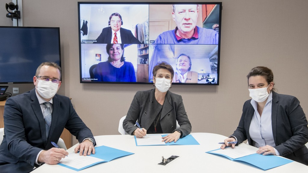 3 people sign an agreement via a zoom call