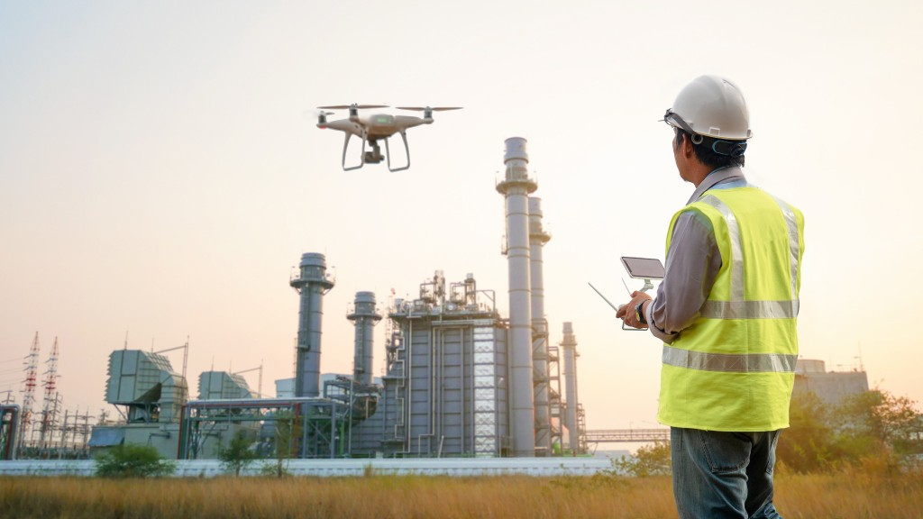 Worker flying a drone near a plant