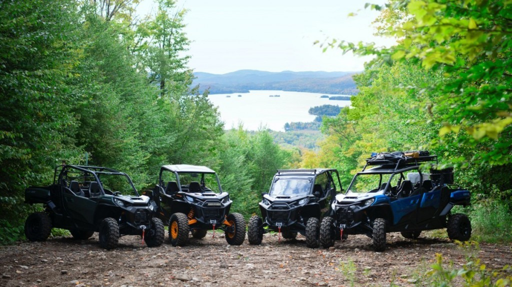 an array of Can-Am Commander vehicles on a forest road