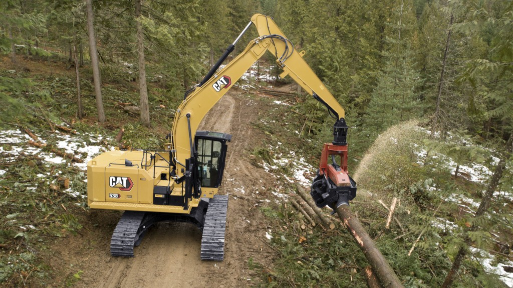 Cat 538 forest machine at work in forest listing logs