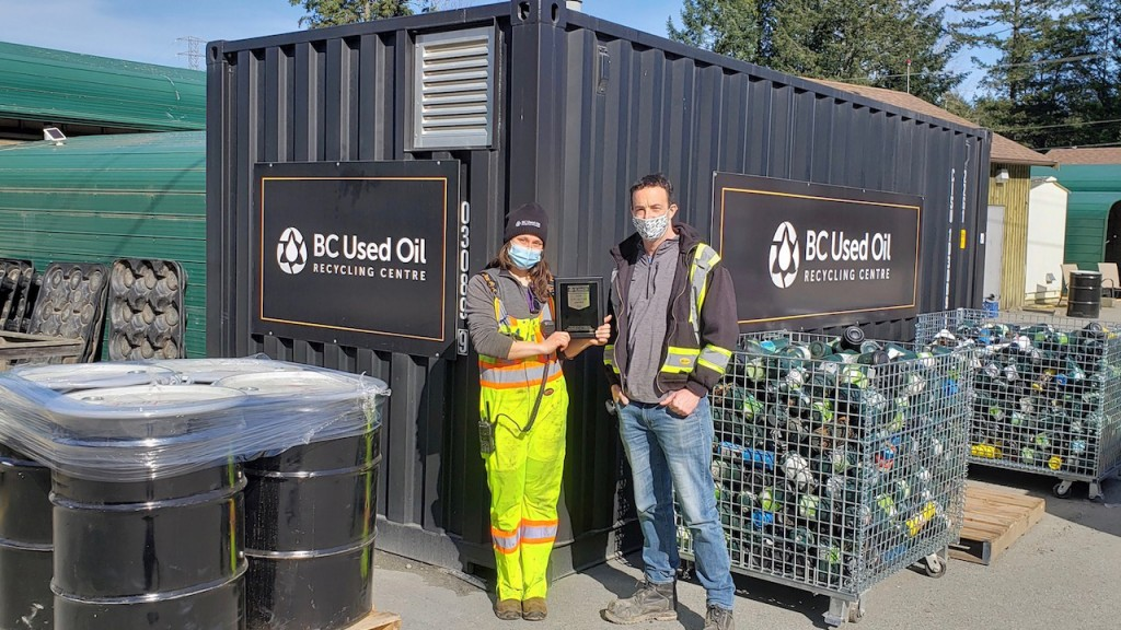 two people in masks stand outside a BC Used Oil recycling centre