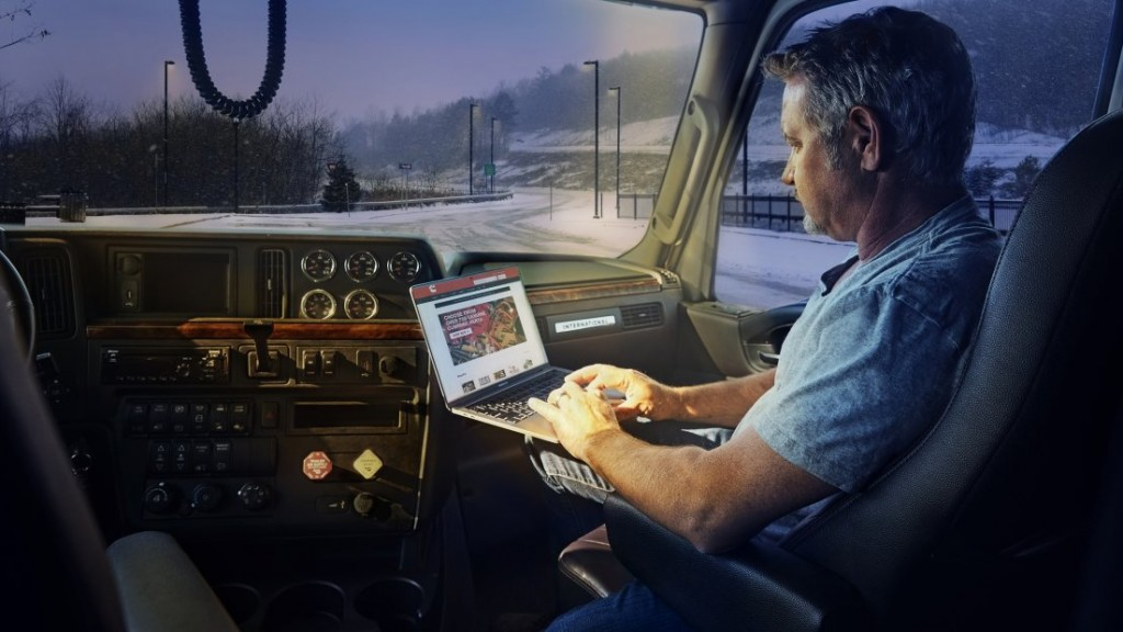man using computer in a truck