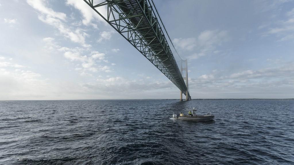 boat below bridge in sea