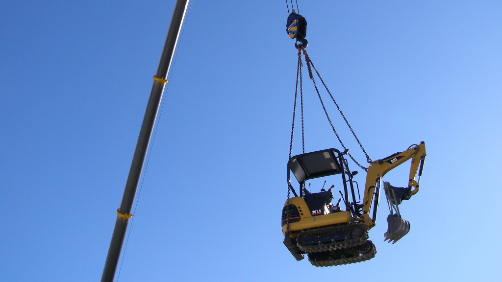 Compact excavator being lifted by crane