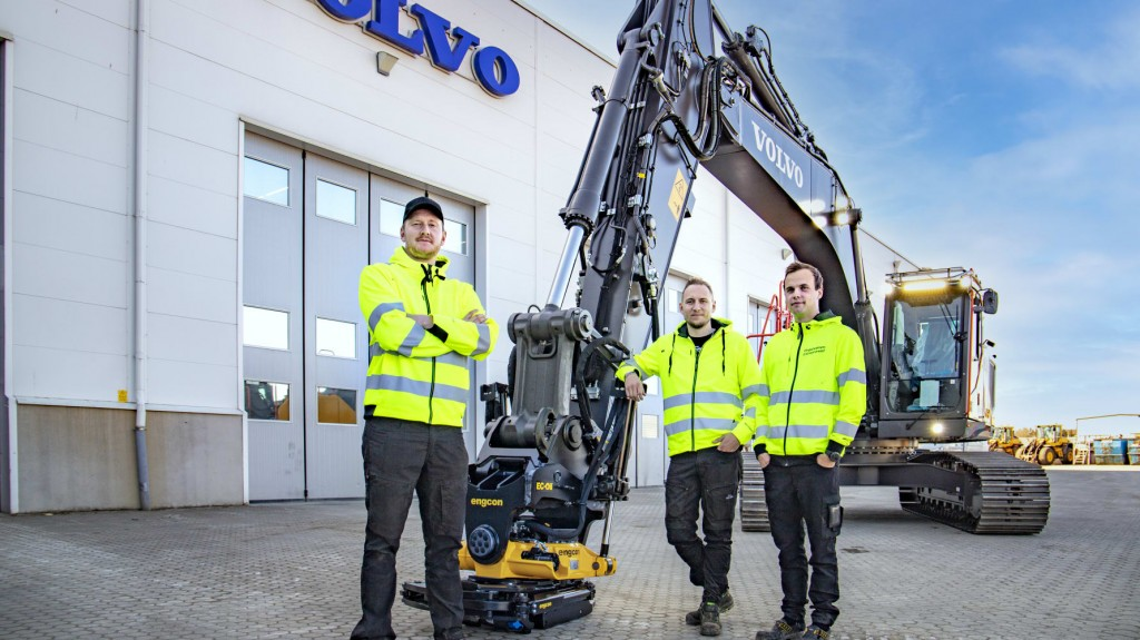 3 men stand next to Volvo CE machine