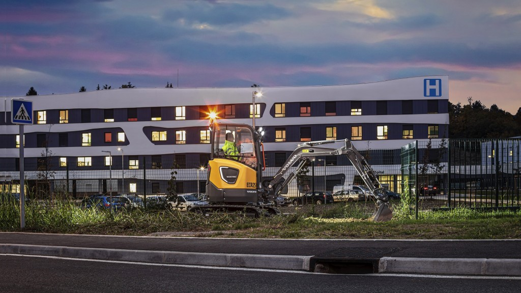 Volvo ECR25 doing work in front of building