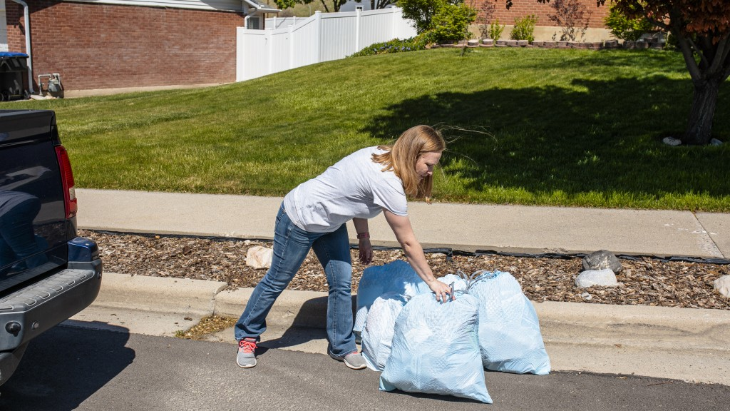 woman putting out Glad garbage bags on curb