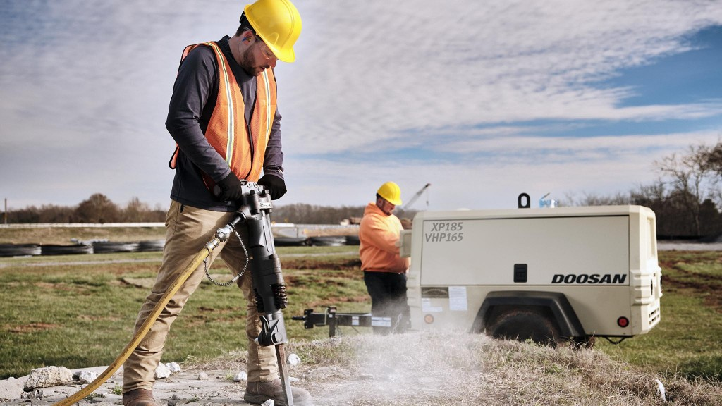 man using a doosan xp185 vhp165 air compressor for a breaker