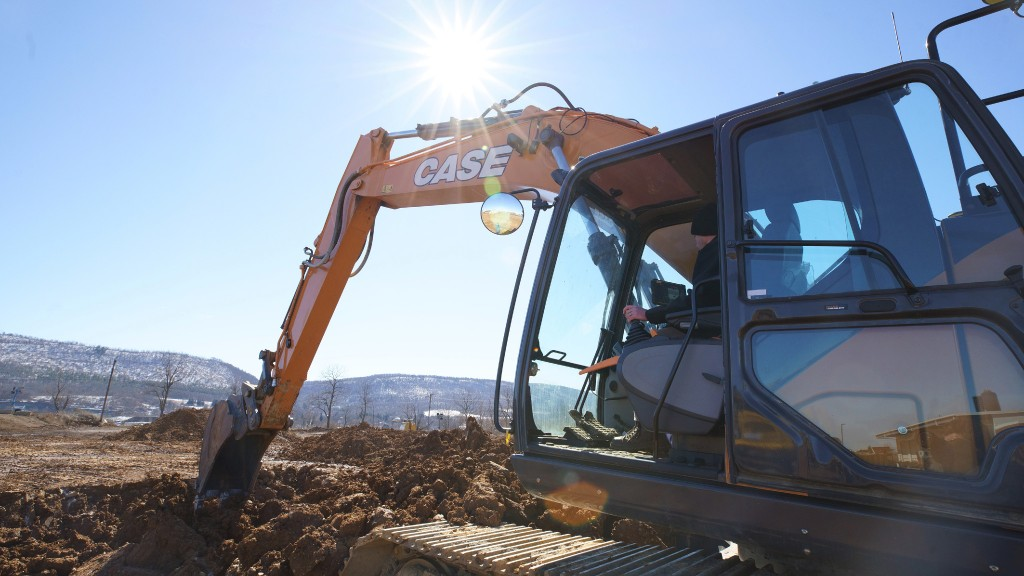 A Case excavator digs a hole on a job site