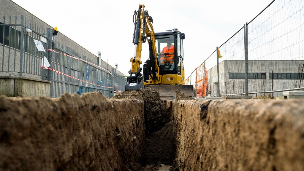 A Cat mini hydraulic excavator digs a trench on a job site