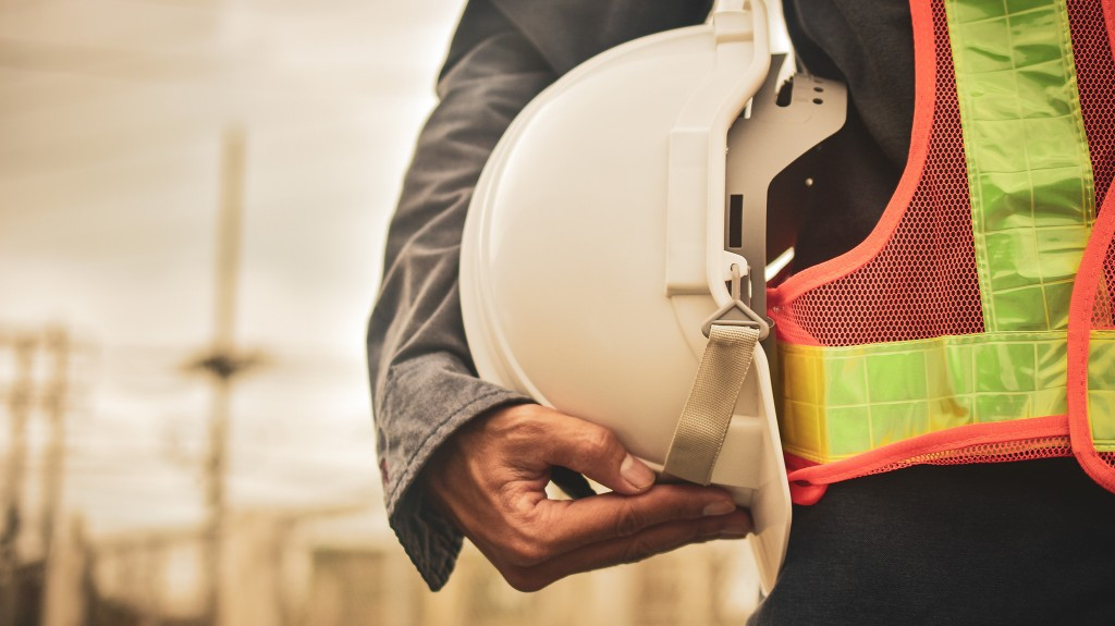 A construction worker holds their helmet