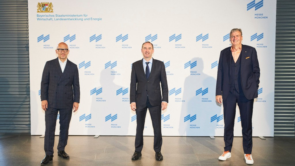 Three high-level employees in suits pose for a photo