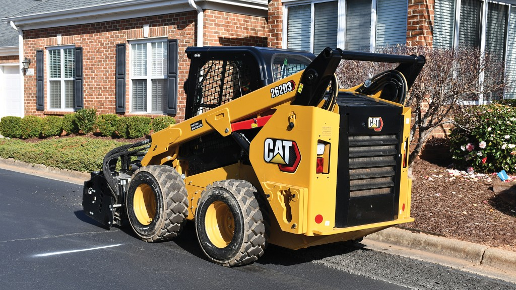 Cat skid steer with cold planer attachment on residential street
