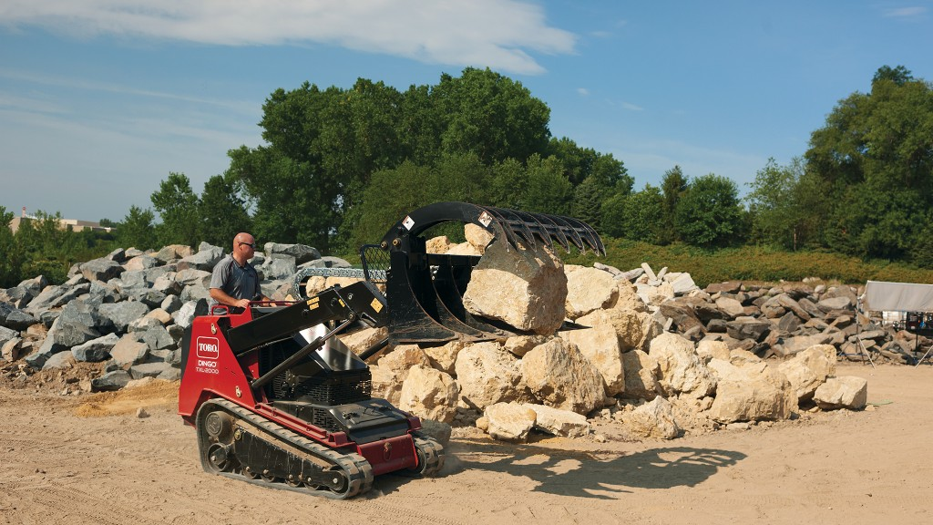 Toro compact utility loader moves large rock with grapple attachment