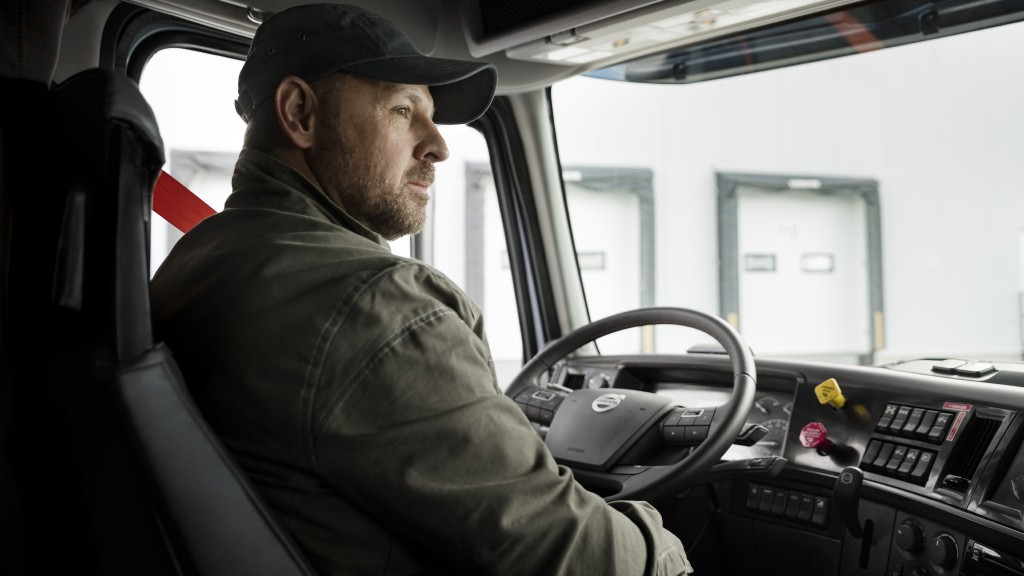 A driver sits in the cab of their truck