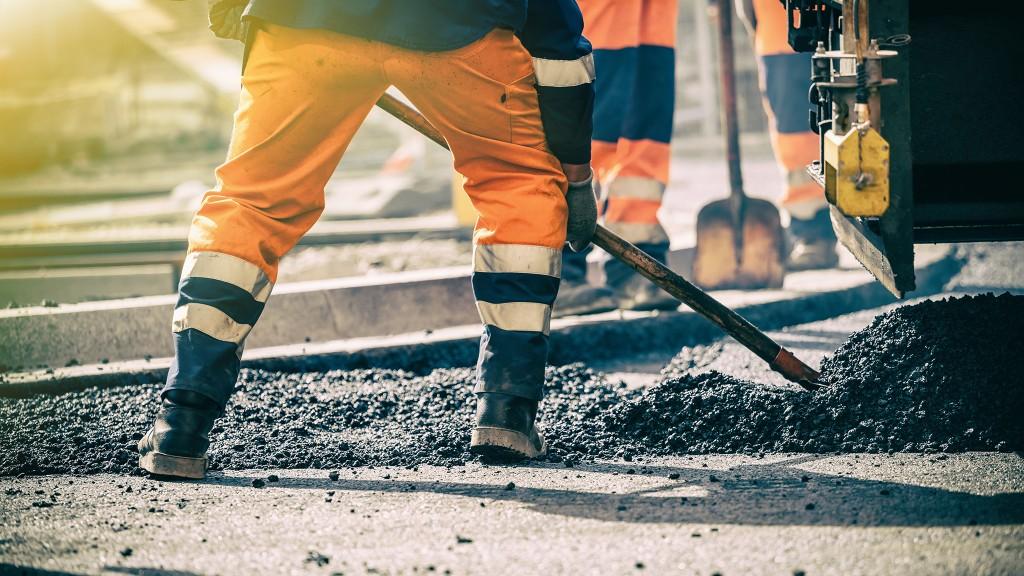 worker shovels asphalt on a paving job