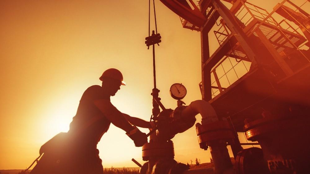 men work on oil rig at sunset