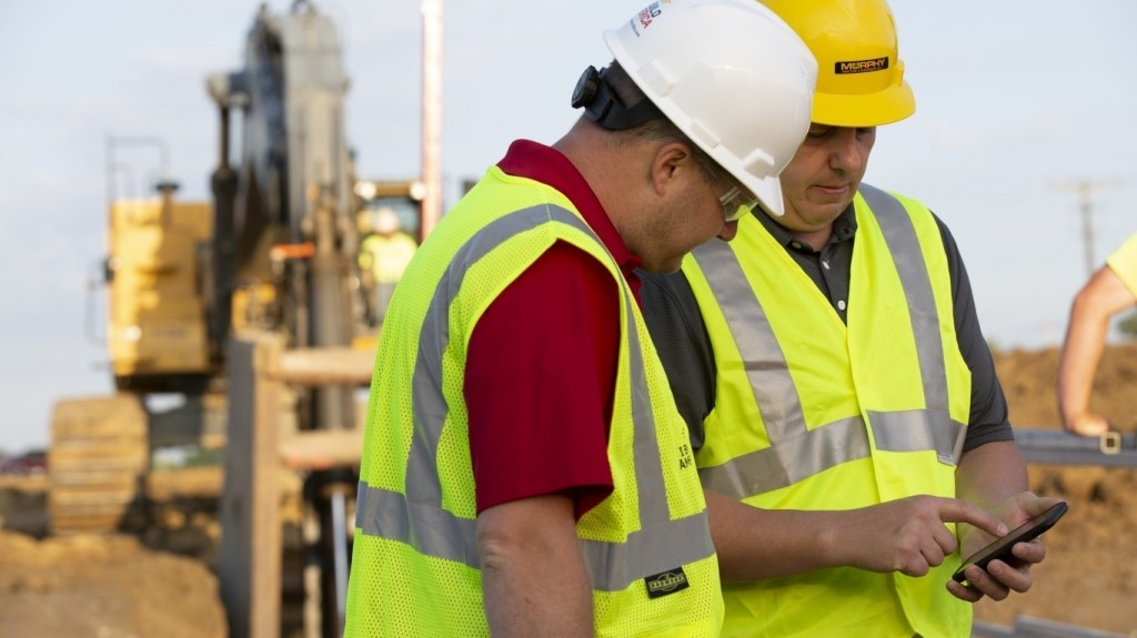 Two workers look at telematics on a tablet
