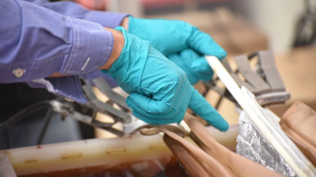 Gloved hands sort through various materials