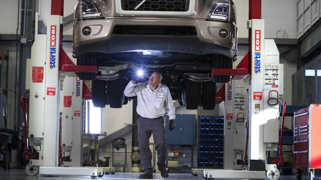 A mechanic works underneath a Volvo truck