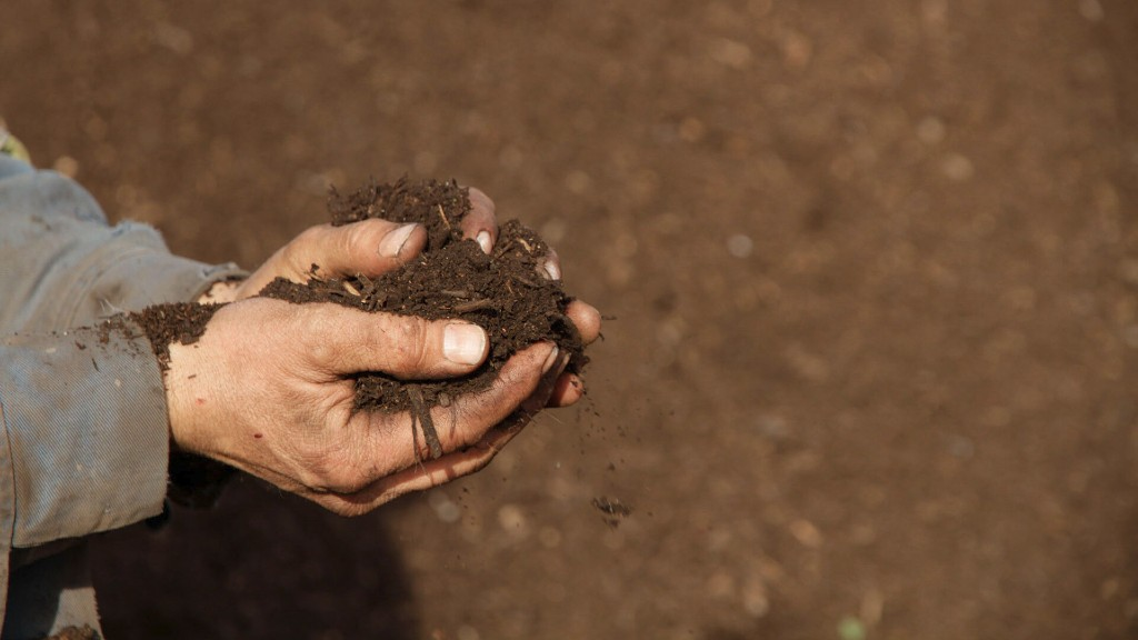 A farmer holds a pile of compost dirt