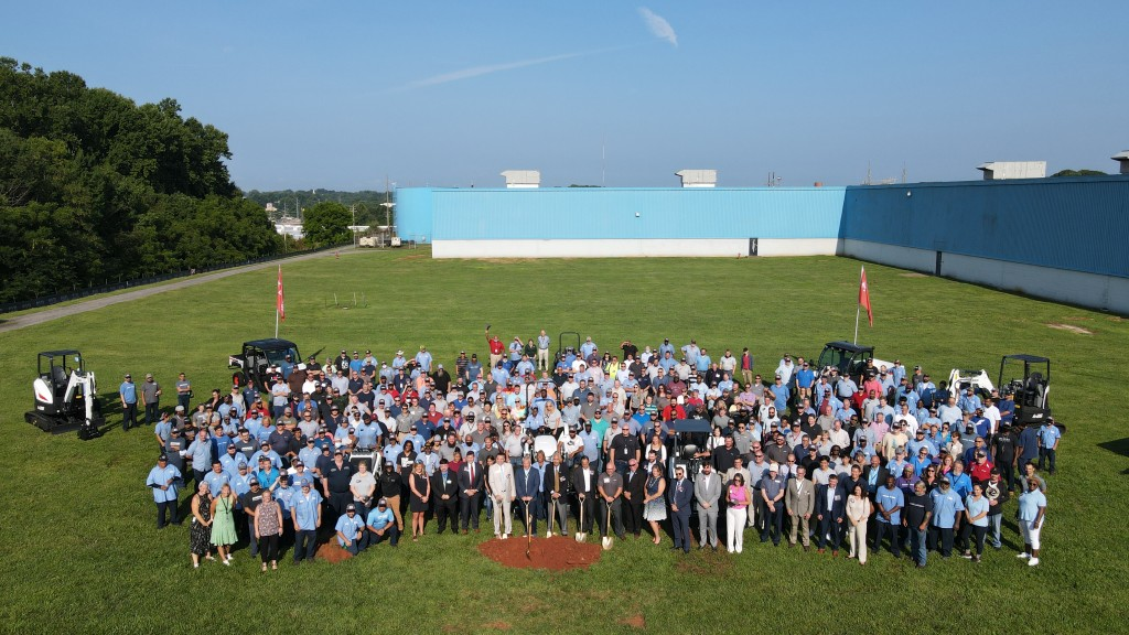 Employees, officials and community and business leaders pose for an aerial photo.