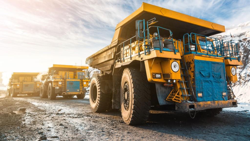 Three mining trucks in a row on a job site