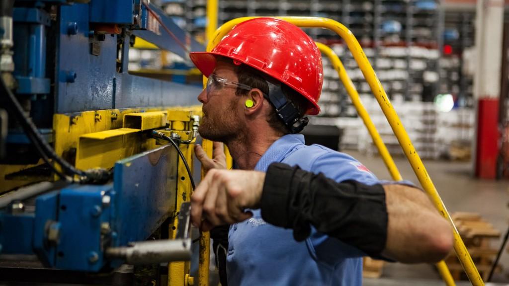 A worker operates a manufacturing machine.