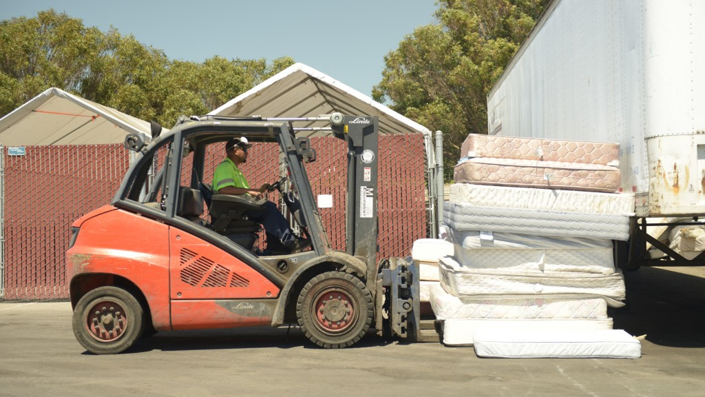 A forklift moves a pile of mattresses.
