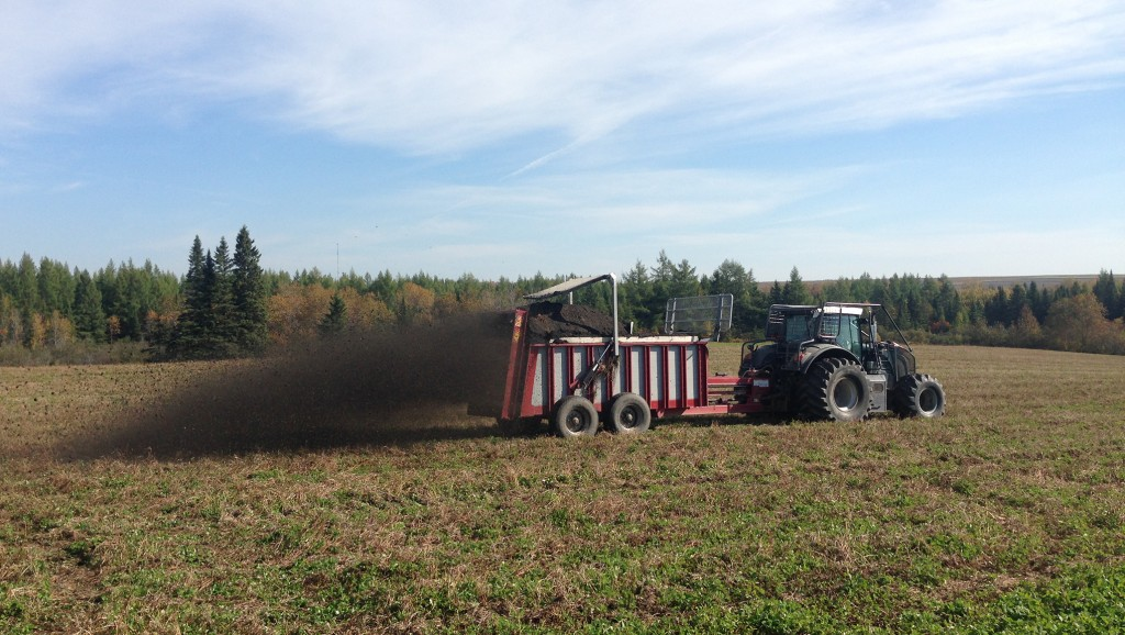 A worker applies compost on a field.