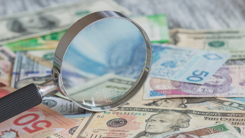 A magnifying glass zooms in on a pile of money