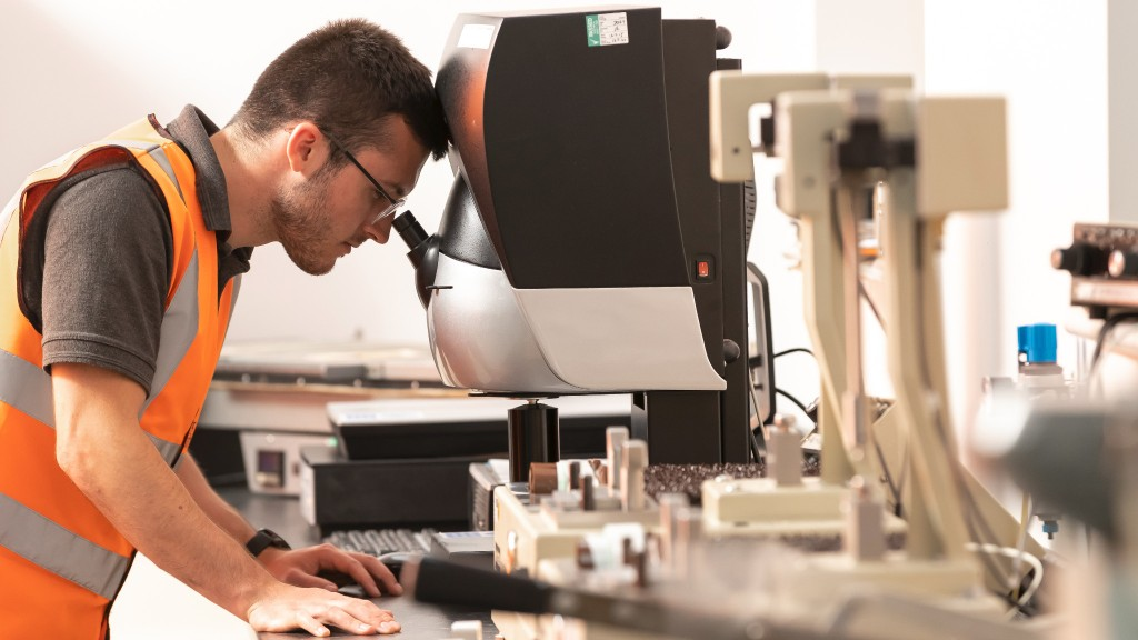 A worker looks into a microscope