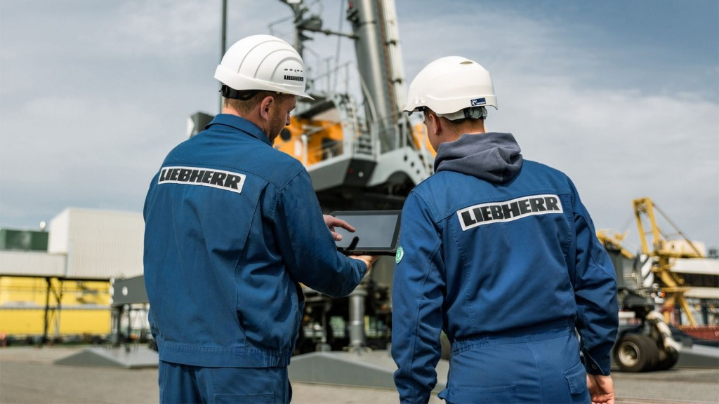 Two Liebherr workers look into a tablet on the job site