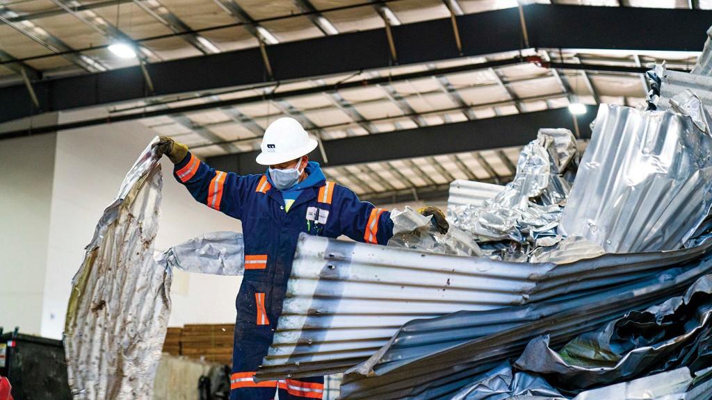 Scrap University student handling scrap metal.