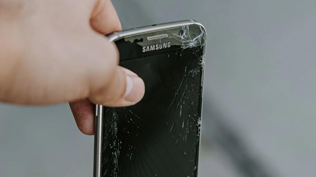 A hand holds a broken smartphone