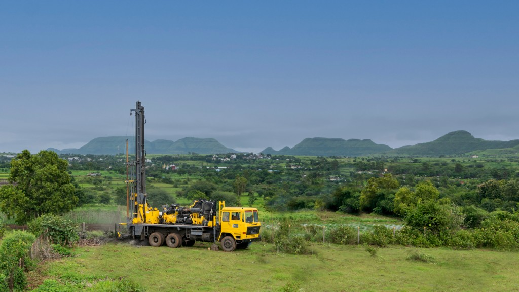 An Epiroc water well drill rig parked on rural hills