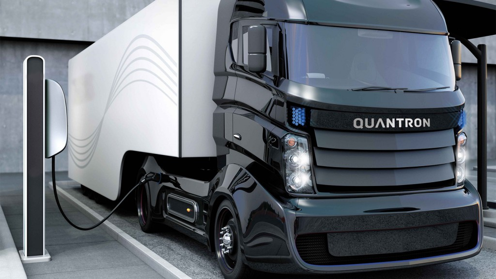 A Quantron truck charging at a charging station