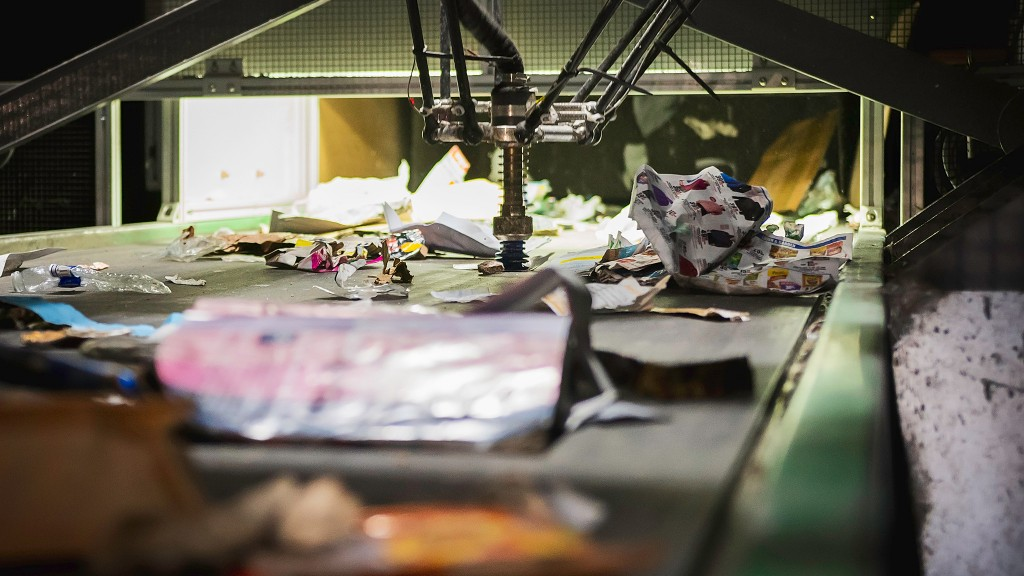 A robot sorts paper on a recycling conveyor