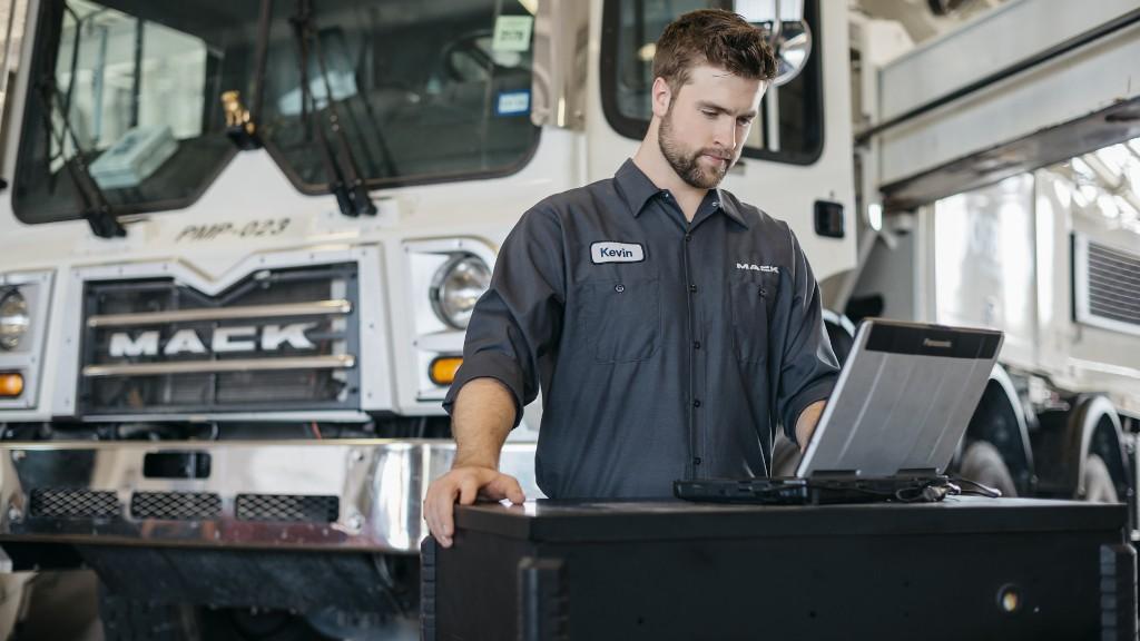 A technician maintains a Mack truck