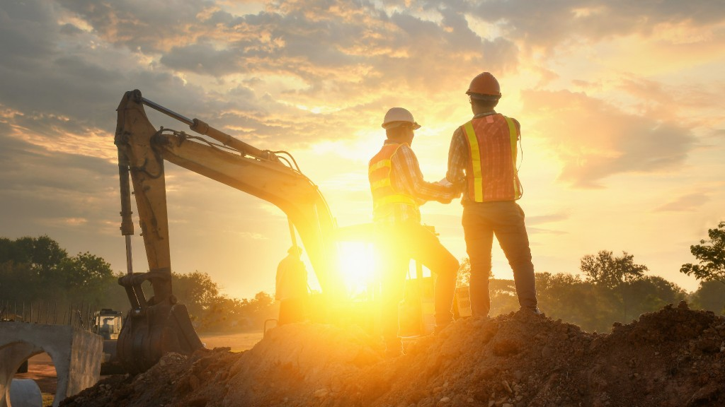 Two construction workers handsake infront of the glowing sun