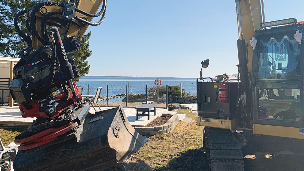 Tiltrotator mounted on excavator landscaping by the beach