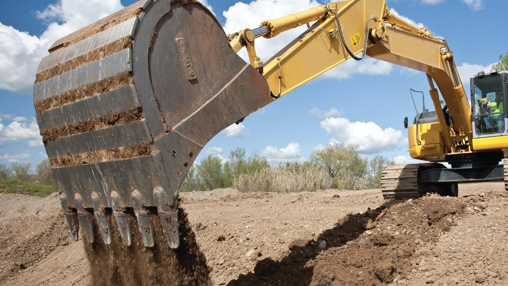 Excavator with bucket resting on trench side
