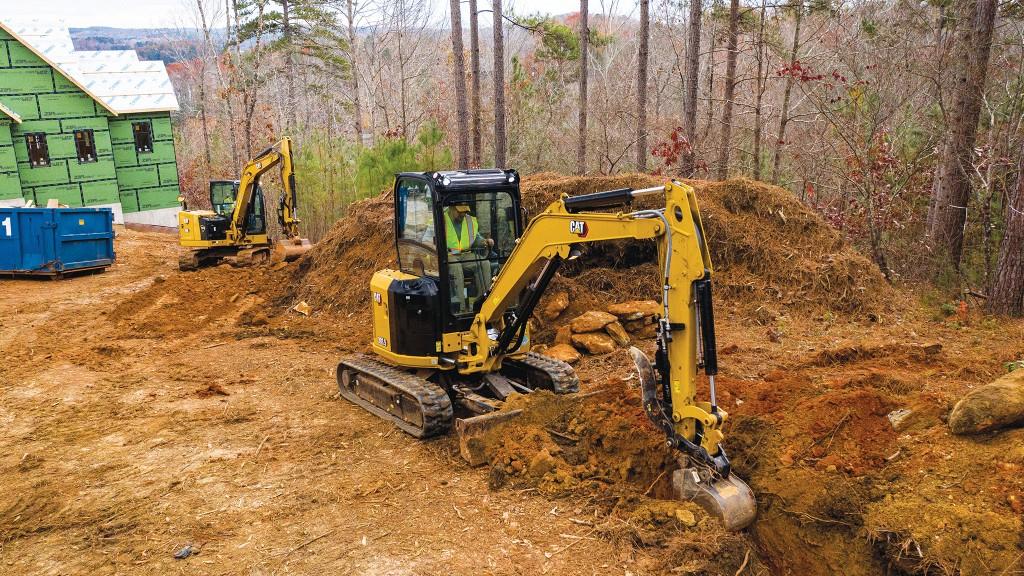 A Cat mini excavator digs on the job site